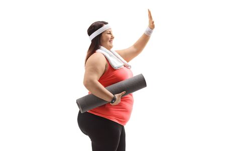 Profile shot of a corpulent woman holding an exercise mat and making a high-five gesture isolated on white background