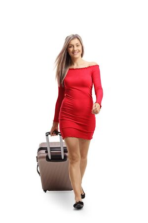 Full length portrait of a young woman in a red dress walking towards camera and pulling a suitcase isolated on white background