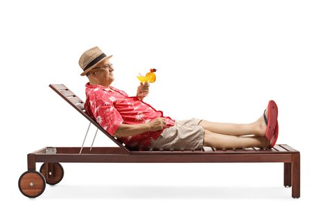 Full length profile shot of a mature man holding a cocktail and relaxing on beach bed isolated on white background