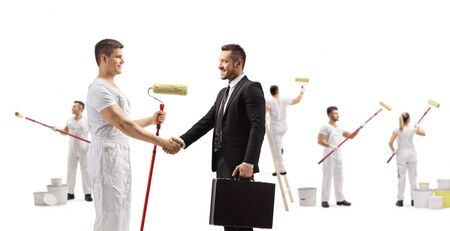 Full length profile shot of a painter shaking hands with a businessman and workers painting isolated on white background