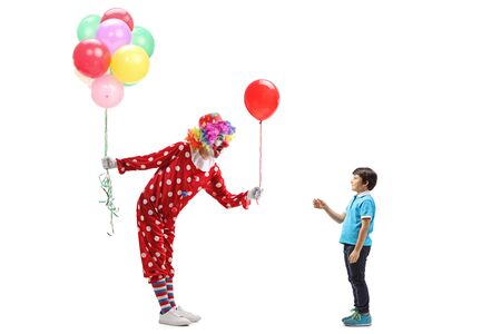 Full length profile shot of a clown giving a balloon to a boy and holding a bunch of balloons in the other hand isolated on white background 写真素材