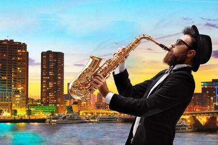 Man playing a saxophone with a view of a city as a background