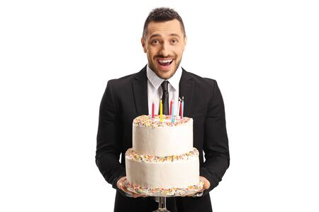 Excited young man in a suit holding a cake with candles and smiling isolated on white background