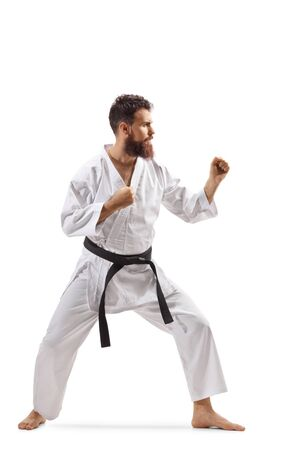 Full length shot of a bearded man in kimono practicing karate isolated on white background