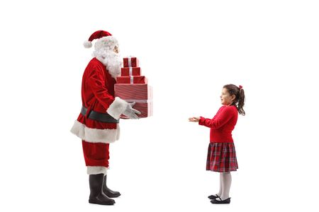 Full length shot of Santa Claus giving a pile of Christmas presents to a happy little girl isolated on white background