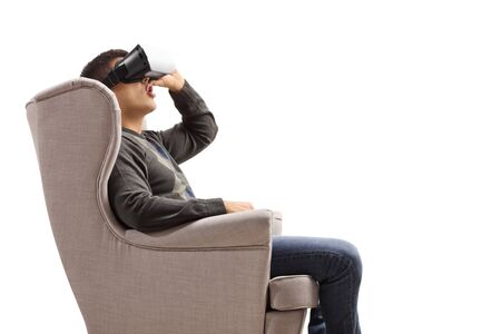 Guy in an armchair using a virtual reality headset isolated on white background 写真素材