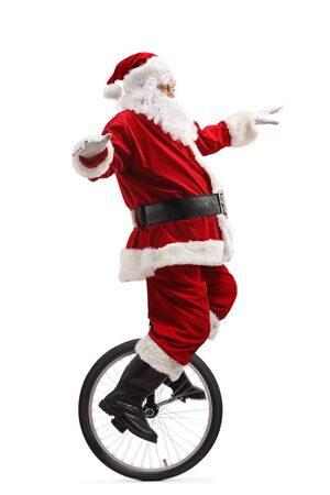 Full length shot of santa claus riding a unicycle and balancing with hands isolated on white background