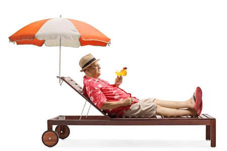 Full length profile shot of a mature male tourist holding a cocktail and relaxing under umbrella isolated on white background 写真素材