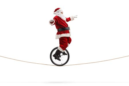 Full length shot of santa claus riding a unicycle on a rope isolated on white background