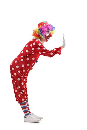 Full length profile shot of a cheerful clown gesturing high-five isolated on white background 写真素材