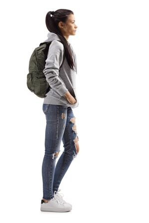 Full length profile shot of a female student with backpack standing isolated on white background 写真素材