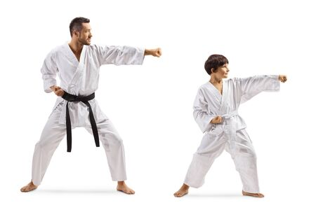 Full length shot of a child practicing karate with instructor isolated on white background