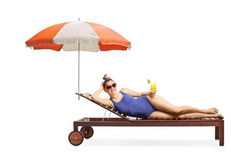 Full length shot of a young woman enjoying on a sunbed with a cocktail isolated on white background