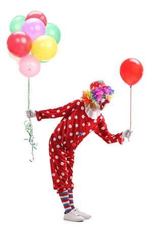 Full length profile shot of a clown giving one balloon from a bunch of balloons isolated on white background
