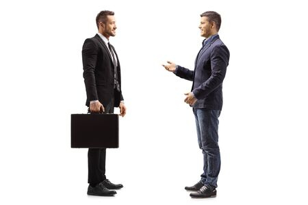 Full length profile shot of two young men talking isolated on white background