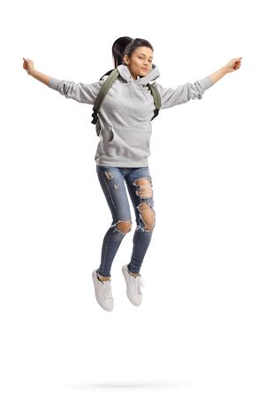 Full length portrait of a female student with backpack jumping isolated on white background