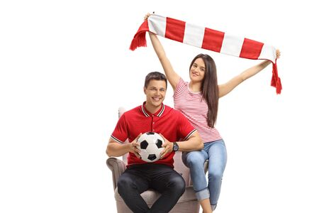 Young male and female soccer fans with a football and a scarf sitting in an armchair isolated on white background