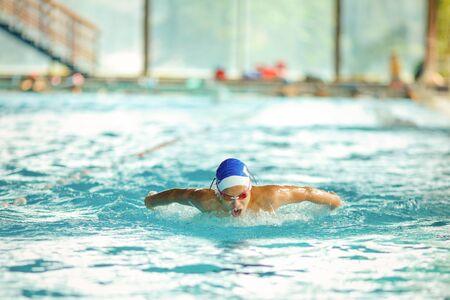 Jonge mannelijke zwemmer die in een pool zwemt