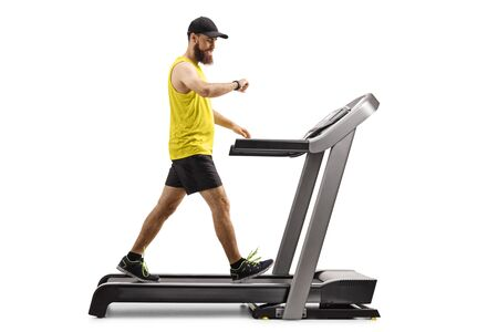 Full length profile shot of a bearded man walking on a treadmill and looking at his smartwatch isolated on white background