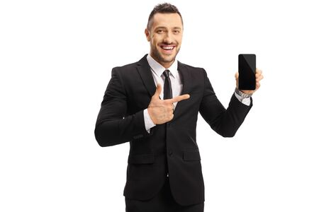 Cheerful young man in a suit holding a mobile phone and pointing at it isolated on white background