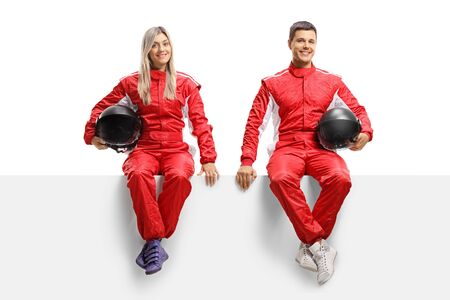 Full length portrait of a male and female car racers sitting on panel in red uniforms isolated on white background