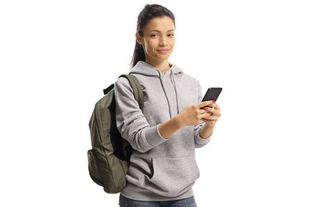 Cheerful female student holding a mobile phone and looking at the camera isolated on white background