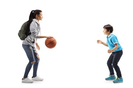 Full length profile shot of a female student and a little boy playing basketball isolated on white background