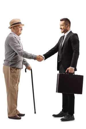 Full length profile shot of an elderly gentleman shaking hands with a young man in a suit with a briefcase isolated on white background