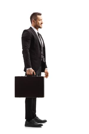 Full length profile shot of a young businessman holding a briefcase isolated on white background