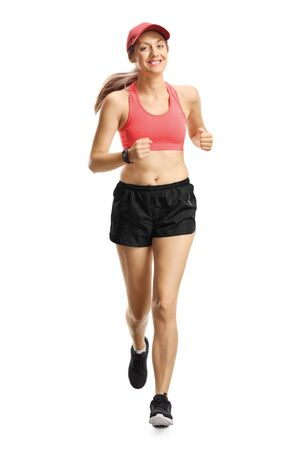 Full length portrait of a young smiling woman in sportswear jogging towards camera isolated on white background