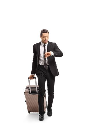 Full length portrait of a businessman with a suitcase going on a business trip and checking his watch isolated on white background