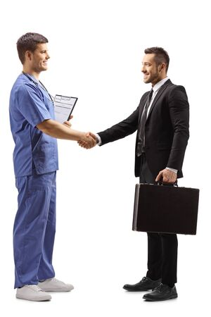 Full length profile shot of a young male doctor in a blue uniform shaking hands with a businessman isolated on white background