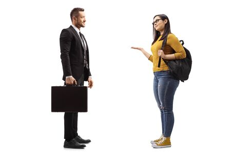 Full length profile shot of a female student with a backpack gesturing with hand and talking to a businessman in a suit isolated on white background