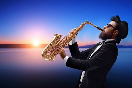 Male jazz musician playing a saxophone with a sunset and water behind him