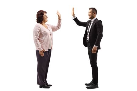 Full length profile shot of a senior woman gesturing high-five with a young man in a suit isolated on white background