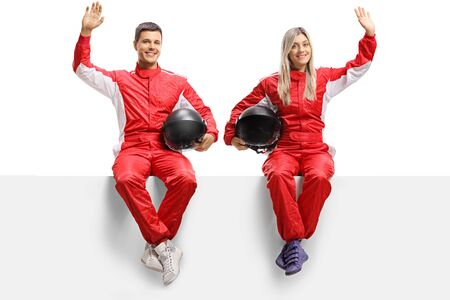 Full length portrait of male and female car racers sitting on panel and waving isolated on white background 写真素材