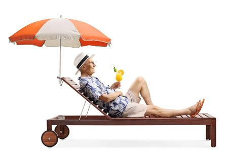 Full length profile shot of a senior man relaxing on a beach bed under umbrella with a cocktail isolated on white background
