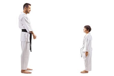 Full length profile shot of a karate kid standing and looking at his karate instructor isolated on white background