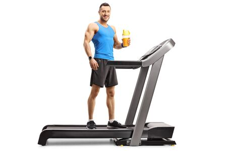 Full length portrait of a muscular man standing on a treadmill and holding a cup of sports drink isolated on white background 写真素材