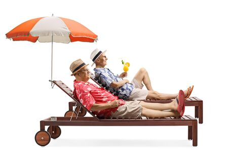 Full length profile shot of two senior men on vacation enjoying a cocktail on a sunbed under umbrella isolated on white background