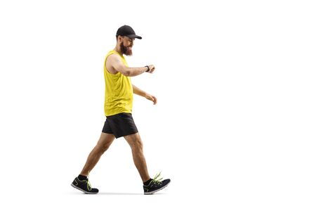 Full length shot of a bearded guy in sportswear walking and looking at his smartwatch isolated on white background 写真素材