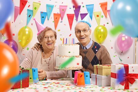 Happy senior couple with a cake at a birthday celebration