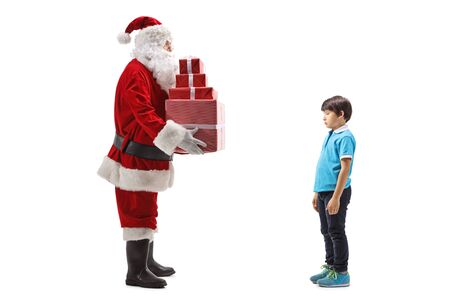 Full length profile shot of Santa Claus giving presents to a sad boy isolated on white background 写真素材