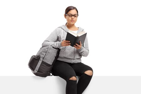 Female student sitting on a panel reading a book isolated on white background 写真素材