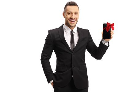 Cheerful man in a suit holding a mobile phone present isolated on white background 写真素材