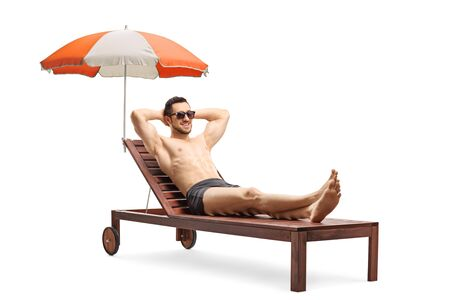 Full length shot of a young man lying on a sunbed under umbrella isolated on white background 写真素材