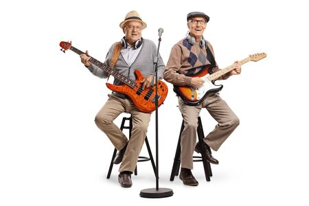 Full length shot of two senior men sitting and playing electric guitars isolated on white background