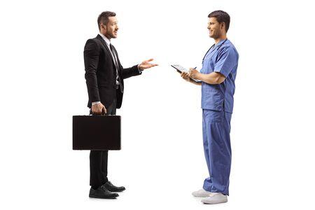 Colpo di profilo integrale di un uomo d'affari con una valigetta che gesticola con la mano e parla con un medico maschio in un'uniforme blu isolato su sfondo bianco