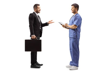Full length profile shot of a businessman with a briefcase gesturing with hand and talking to a male doctor in a blue uniform isolated on white background