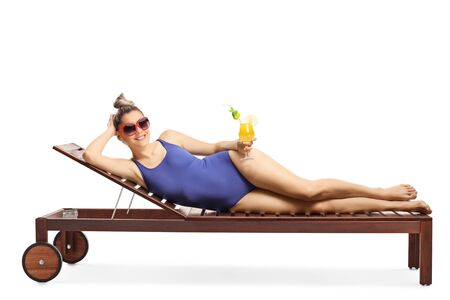 Full length shot of an attractive blond woman with sunglasses lying on a sunbed and holding a cocktail isolated on white background